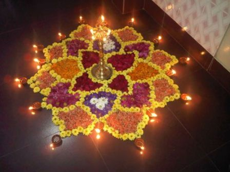 Rangoli designs with flowers and burning diyas