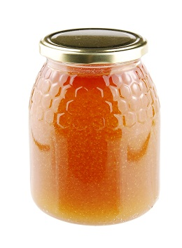 Homemade honey in a glass jar on white