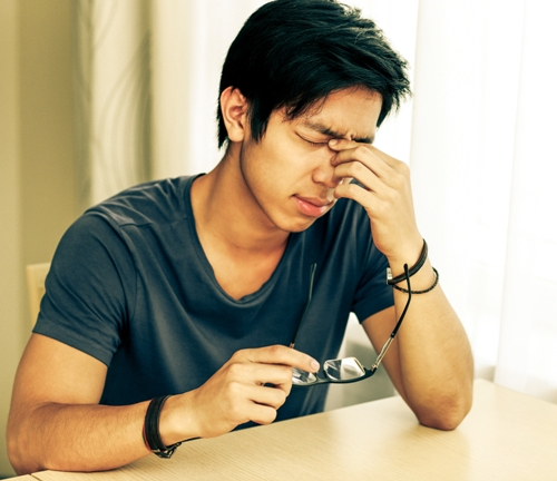 Tired asian man with eye pain holding glasses in hand