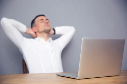 Tired businessman sitting at the table with laptop in office. Focus on laptop