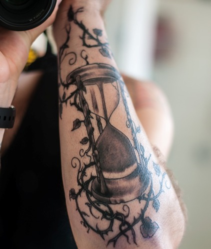 Sand and times within an arm tattoo