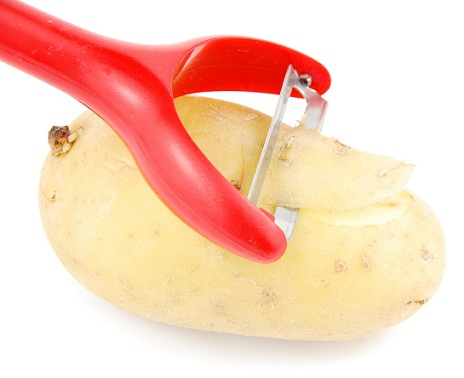 Peeling a potato with peeler on white