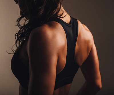 Muscular back of a woman in sportswear