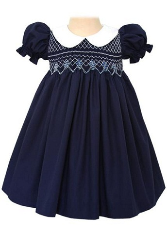 67ccd83a1 This classic cotton navy dress features white Peter Pan collar with short  elastic puff sleeves. The bodice is hand smocked with white and it has  buttons at ...